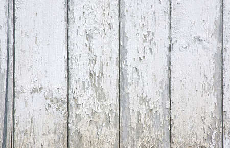 eyesore: The weathered surface of white paint that is peeling on an exterior wall. Stock Photo