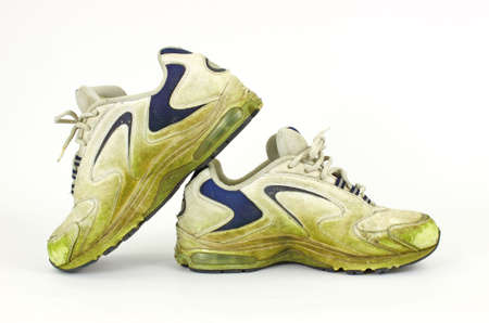 An old pair of grass stained sneakers on a white background. photo