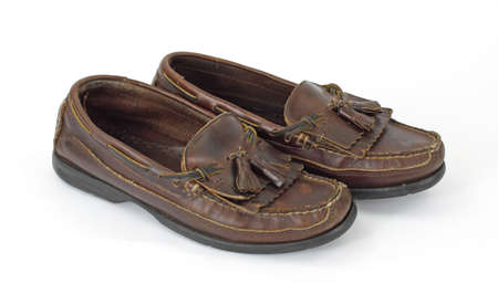 loafers: An old worn pair of mans loafers with tassels on a white background.