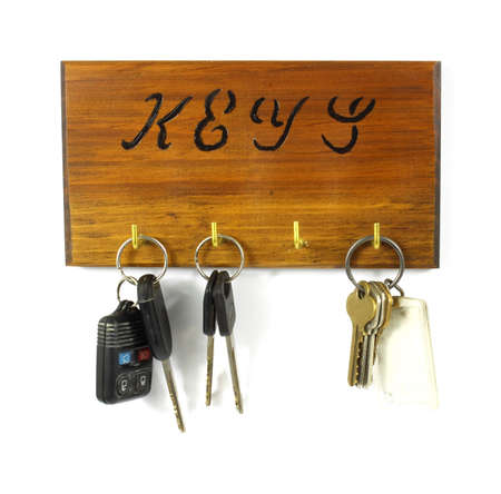 Wood key rack holding three sets of keys on a white background. Stock Photo