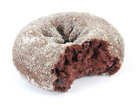 A bitten freshly baked chocolate donut with sugar sprinkled on the surface.