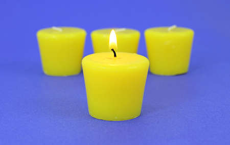 Four citronella candles with the one in the foreground lit and the three in the background out of focus slightly on a blue background. photo