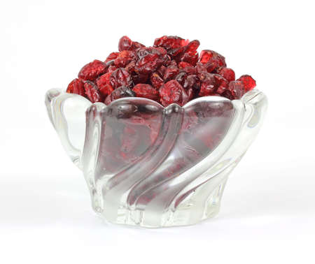 A dish of sweetened dried cranberries on a white background.