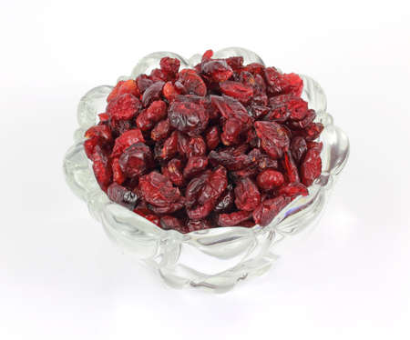 A bowl of sweetened dried cranberries on a white background.
