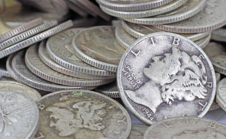 silver coins: A close view of old silver bullion with a Mercury dime as the focal point.