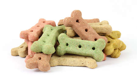 shaped: A small group of different colored dog biscuits on a white background.