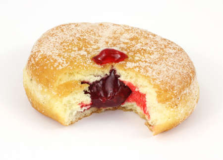 A bitten raspberry jam filled donut with sugar sprinkled on the surface.