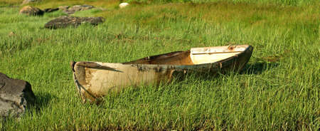 discarded: An old discarded fiberglass skiff on a grass covered banking.