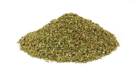 A large amount of dried cut and chopped marjoram herb on a white background.
