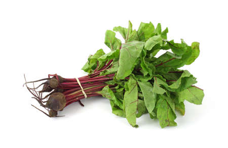 Several beet greens with small beets on a white background.