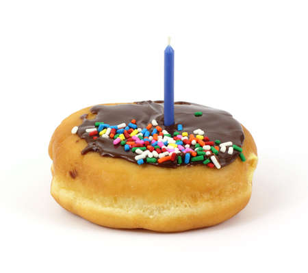 jimmies: A cream filled donut with chocolate icing and jimmies that has a single birthday candle on a white background.