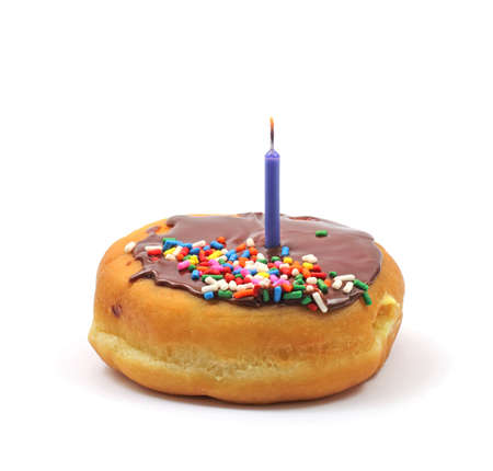Filled donut with chocolate icing and sprinkles and a single birthday candle on a white background. photo