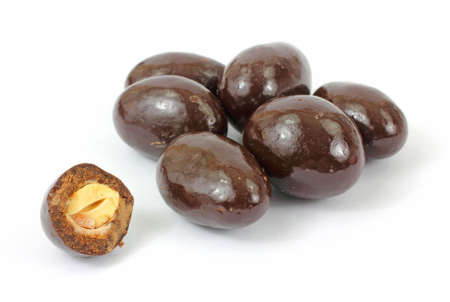 Several milk chocolate covered almonds with one bitten on a white background.