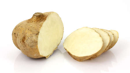 A jicama root that has been cut on a white background.