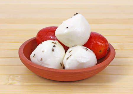 A side dish of marinated mozzarella cheese balls and tomatoes in a dish. photo