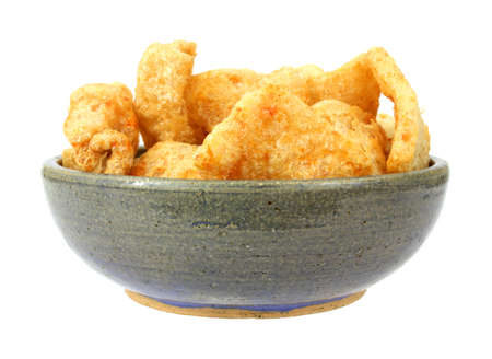 rinds: An old stoneware bowl filled with barbecue seasoned pork rinds in on a white background. Stock Photo