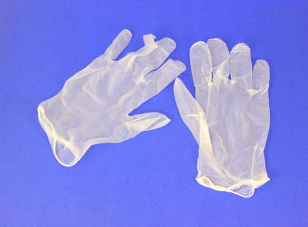 A pair of vinyl gloves on a blue background.