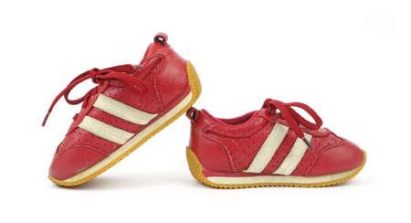 スニーカー: 白い背景の上に使用される幼児のスニーカーのペア。