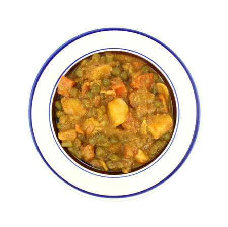 A bowl of mixed vegetables in curry sauce on a white background.
