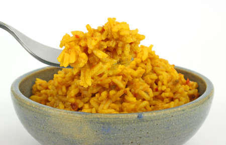 stoneware: A large serving of spicy seasoned rice in a stoneware bowl with a portion on a fork. Stock Photo