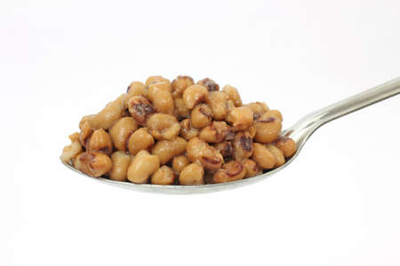 A large serving spoon filled with black eyed peas on a white background.