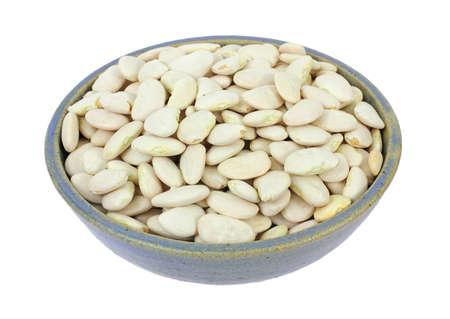 Een kom gevuld met grote lima bonen op een witte achtergrond.