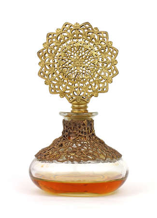 Vintage perfume bottle with gold filigree top and amber colored liquid. photo