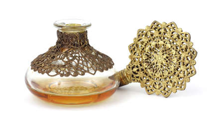 Vintage perfume bottle with gold filigree stopper on its side with amber colored liquid.