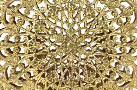 cor: Close view of delicate gold filigree design.