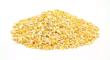 Small pile of cracked corn bird food on a white background.