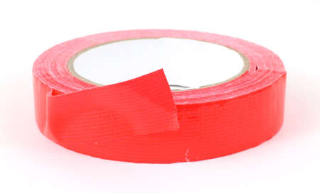 masking: A roll of red duct tape lying on a white background.