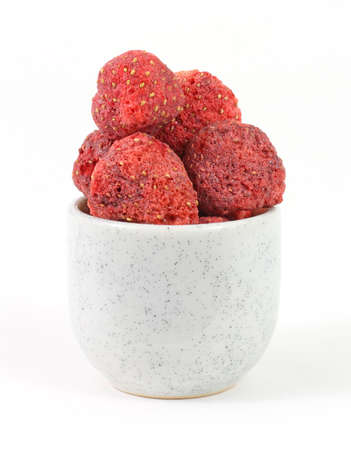 Several freeze dried strawberries in a small dish on a white background.