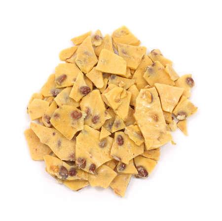 흰색 배경에 땅콩 부서지기 쉬운 캔디의 큰 금액.
