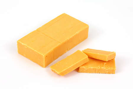 A bar of sharp cheddar cheese with several slices on a white background.