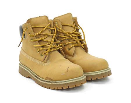 zapatos de seguridad: Un par de botas de trabajo usados sobre un fondo blanco. Foto de archivo