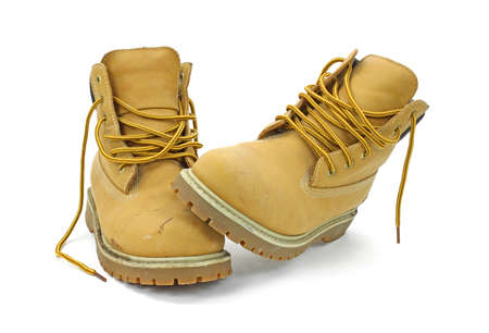 A pair of used work boots that are unlaced on a white background. 스톡 콘텐츠
