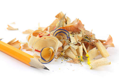A small mound of pencil shavings with a sharpened lead pencil on a white background.  photo