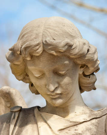 The face of a sad angel statue in downward cast. photo