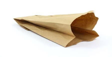 使用する茶色の紙袋、白い背景上にややオープン畳んだ。 写真素材