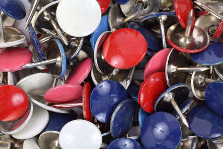 A very close view of several red blue and white thumbtacks.