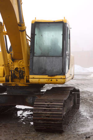 construction machinery: The cab of a backhoe with raindrops on a damp and foggy day.
