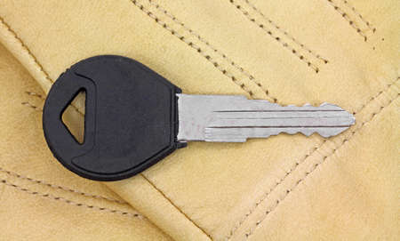 A single new car key on a pair of leather driving gloves.