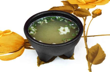 Serving of Miso soup in a black bowl on a floral tablecloth. photo