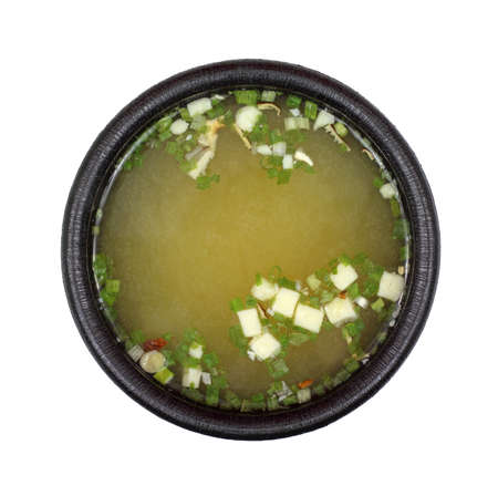 Serving of miso soup in a black bowl on a white background. Stock Photo