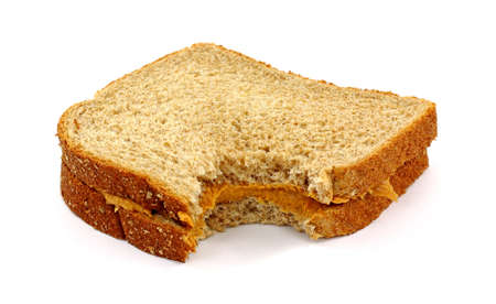 A freshly made peanut butter sandwich with wheat bread that has been bitten on a white background.
