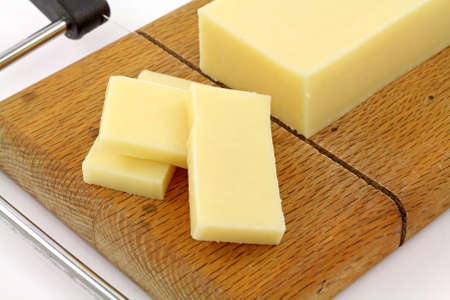 Very close view of a bar of reduced fat sharp cheddar cheese that has been sliced on a wood cutting board. photo