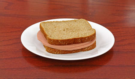 A bologna sandwich on wheat bread in a white dish on wood tabletop. photo