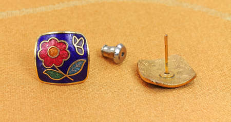 tissu or: A pair of earrings with a bright colorful floral pattern on a gold cloth, with one earring upside down with the post upright.