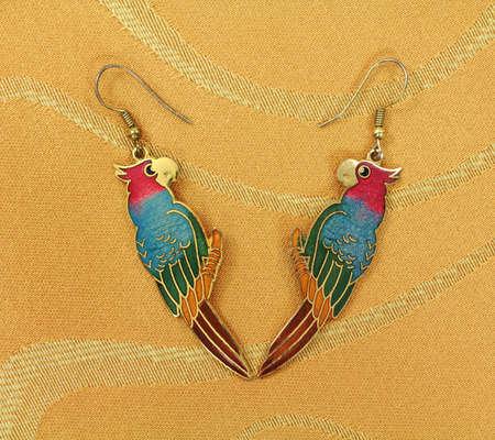 tissu or: Deux boucles d'oreilles color�es perroquets vintage sur un fond de drap d'or.