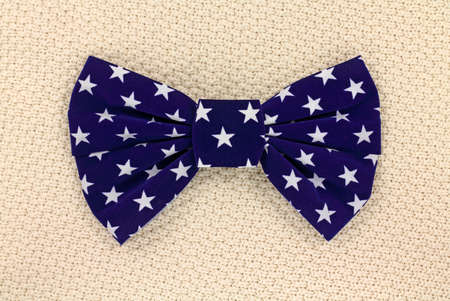 A large blue bow tie with white stars on a textured background. Banco de Imagens